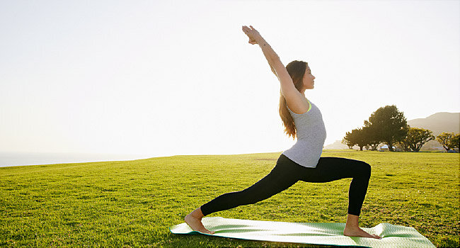 Someone in athletic clothing doing a yoga pose while standing on a yoga mat in a grassy field