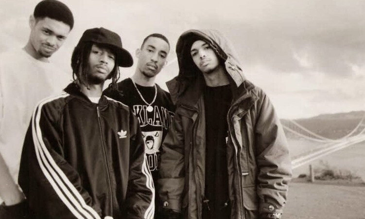 A black and white portrait of the hip hop group The Souls of Mischief standing together in an outdoor setting