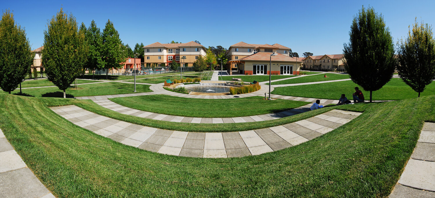 A wide-angle view of the outdoors area of on-campus housing including grass areas, trees, walking paths, and a fountain