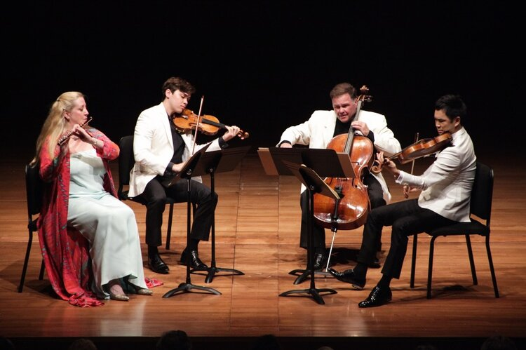 A group of 4 people sitting while playing wind and string instruments on a well-lite stage
