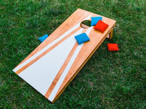 A wooden corn hole board with blue and red beanbags on top of green grass