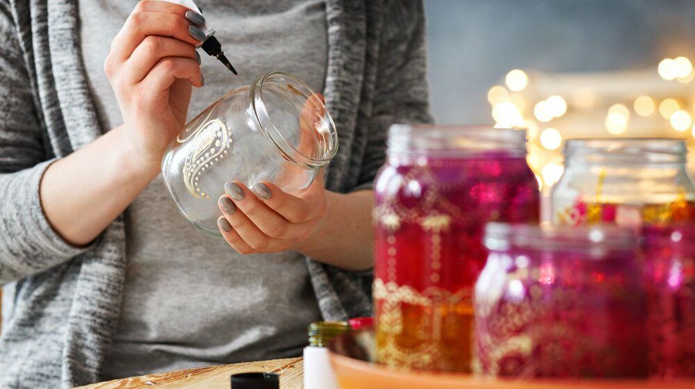 A person in grey clothes writing/drawing in pen on a glass jar with maroon-colored jars in the foreground