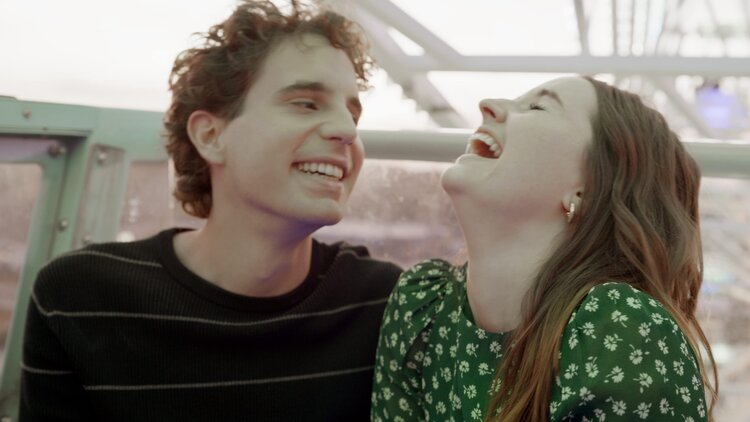A still from the film 'Dear Evan Hansen' of two people laughing while on a ferris wheel ride