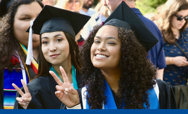 Two graduates wearing graduation caps and gowns smile and pose with finger peace signs