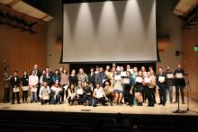 A large group of scholarship recipients posing on stage at the Scholarship Showcase
