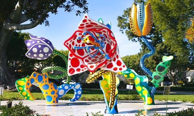 Three colorful outdoor art sculptures surrounded by greenery