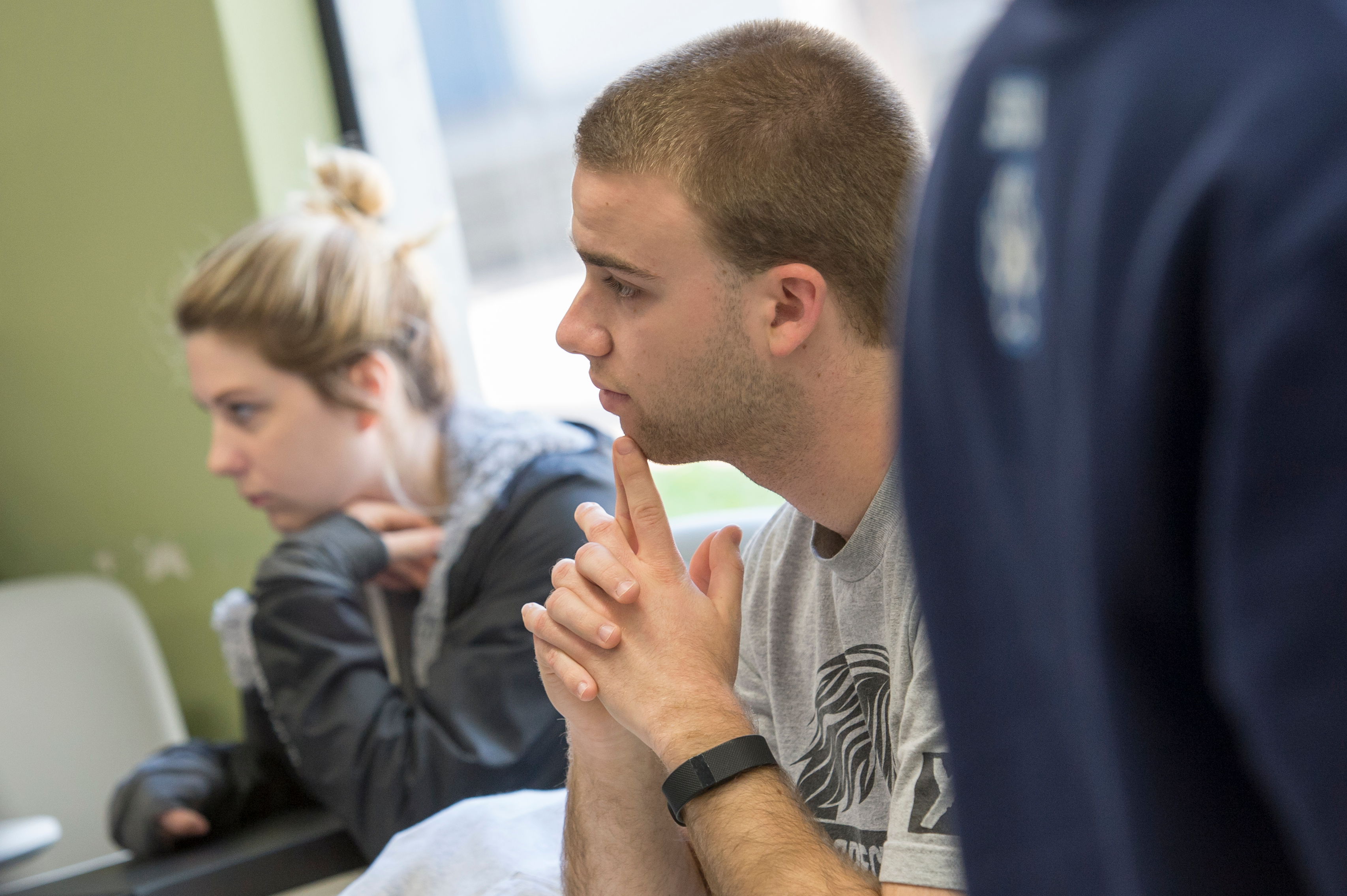 Student seated with elbows on table and clasped fingers on chin listens