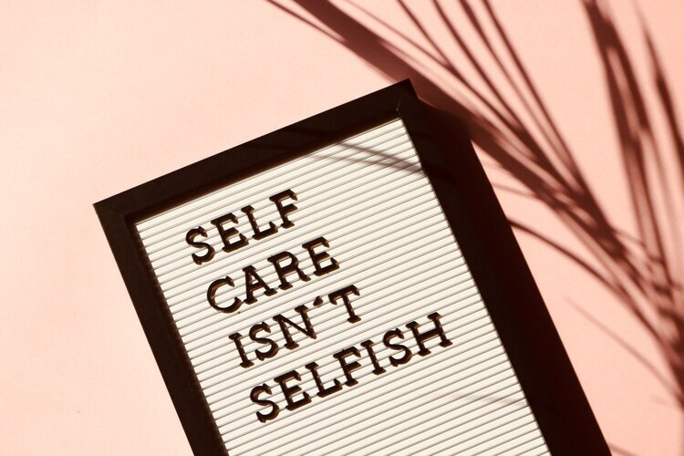 """A sign that reads 'Self Care Isn't Selfish"""" in black letters in front of a pink shadowy background"""
