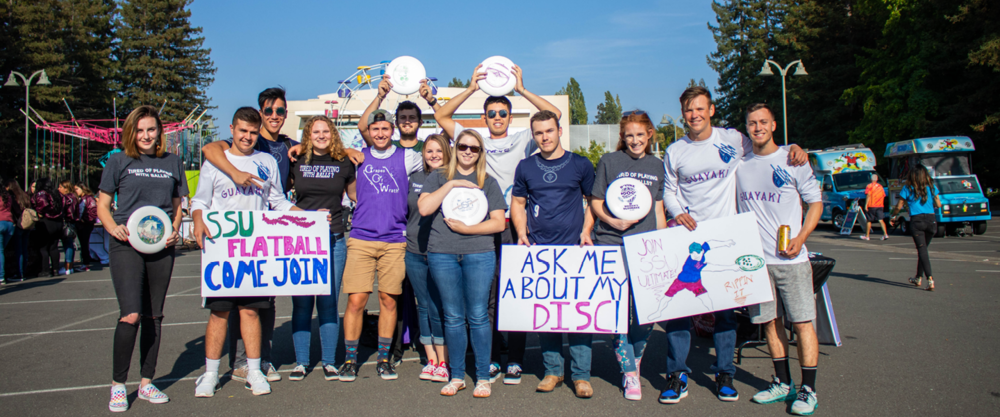 A large group of students posing together outdoors holding colorful handmade signs