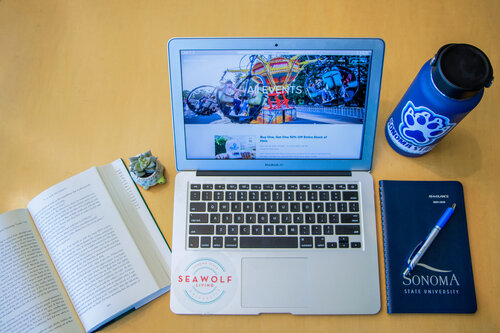 A tabletop featuring a thermos featuring a Seawolf paw, a Sonoma State University notebook, a pen, an open book, and an open laptop with a Seawolf Living sticker on it