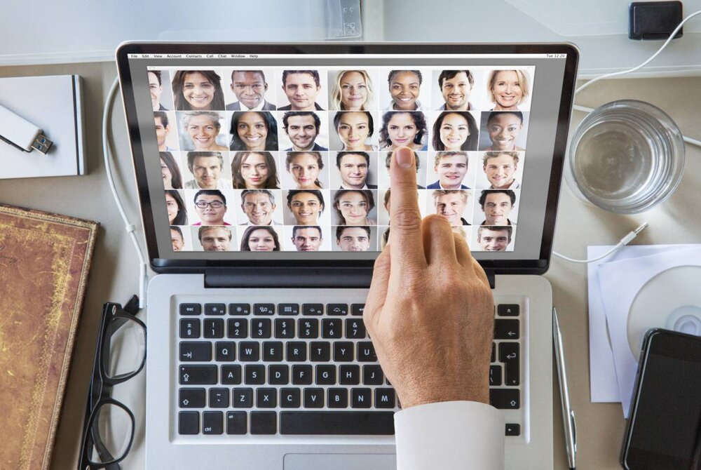 A hand pointing to the screen of a laptop featuring multiple images of different people's faces