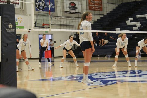 People on the women's volleyball team playing volleyball in an indoor setting