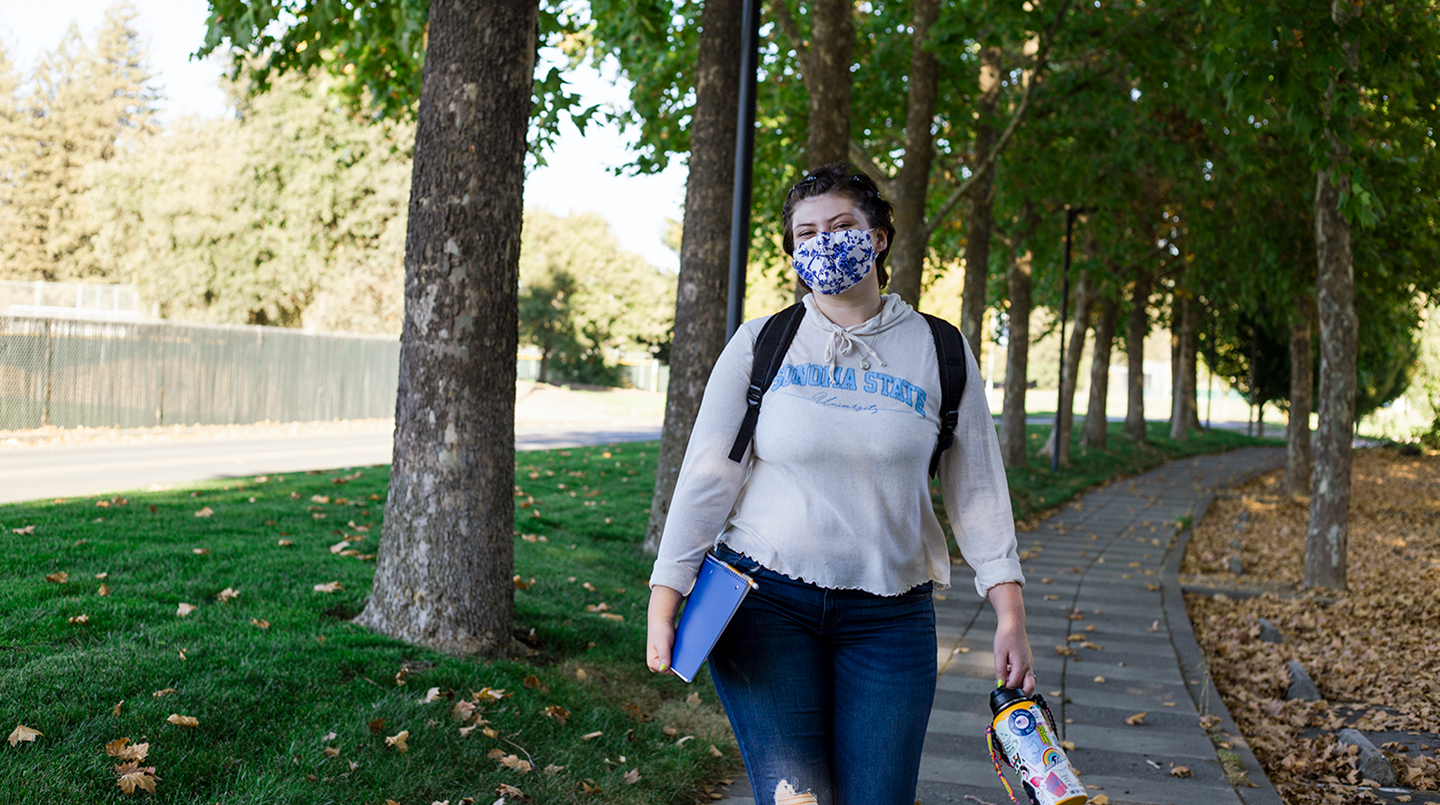 Student holding books and water bottle walks down tree-lined sidewalk