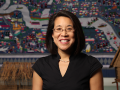 A portrait of Dr. Erika Lee smiling in a black shirt in front of artwork and artifacts