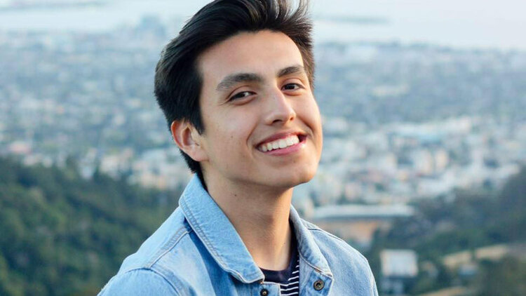 A portrait of Isaias Hernandez smiling in a denim shirt in front of a city skyline