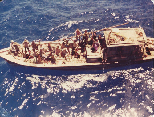 A still from the film 'Finding The Virgo' featuring an aerial view of multiple people standing on a wooden boat