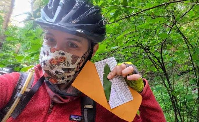 Someone wearing a mask, bicycle helmet, and outdoor gear while holding/posing with some paperwork and a leaf