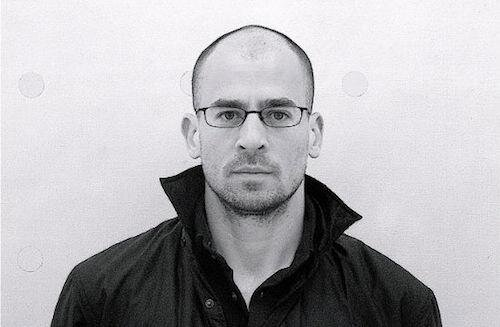 A black and white portrait of Andrew Zawacki wearing glasses and a black collared jacket in front of a white background