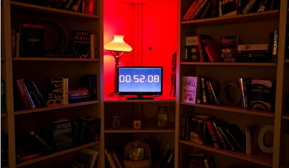 A darkly lit room with filled bookshelves, a red lamp, and a computer screen with the digits '00:52:08' displayed on it