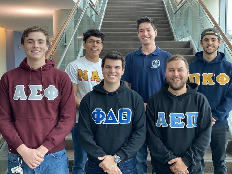 A group of six fraternity members standing in two rows and smiling while wearing different fraternity sweatshirts