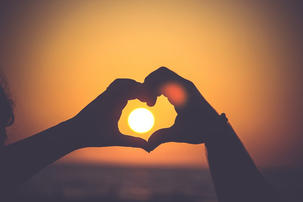 Silhouette of two hands coming together to form the shape of a heart with the sunset in the background