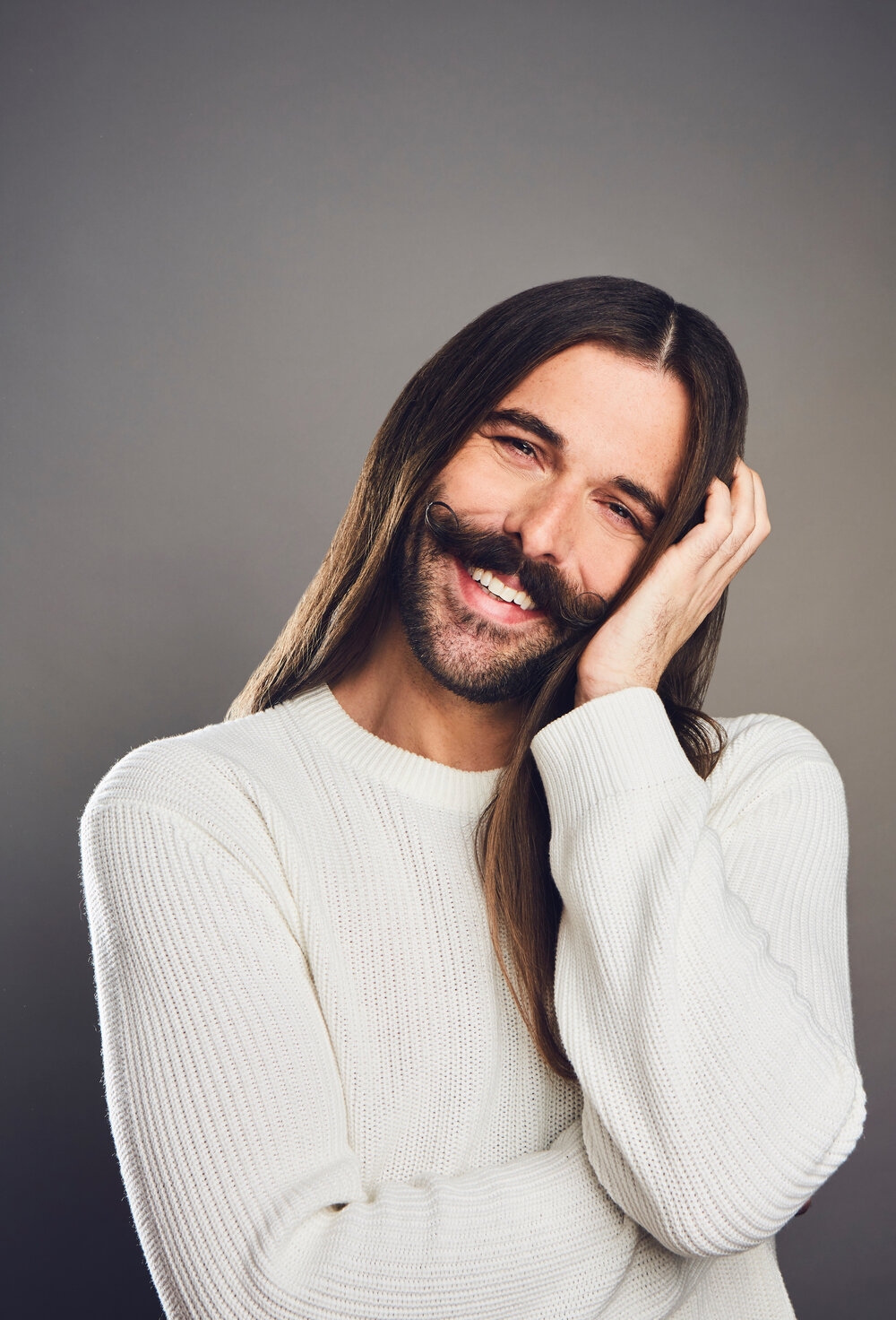 Portrait of Jonathan Van Ness smiling while wearing white sweater in front of a faded grey background
