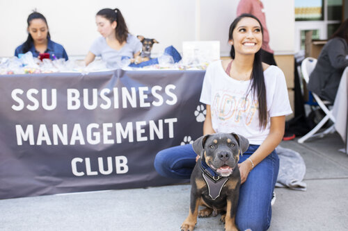 """A student smiling and posing with a dog in front of a table display featuring a banner that reads """"SSU Business Management Club"""""""