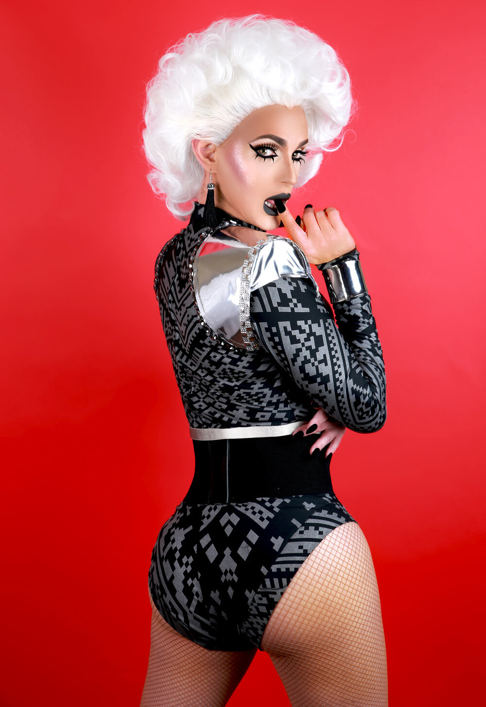Portrait of Cynthia Lee Fontaine in a black and silver outfit in front of a red background