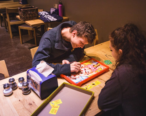 Two student playing a board game at Lobo's