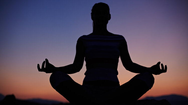 The silhouette of someone in a meditative pose in front of an orange, purple, and blue sunset