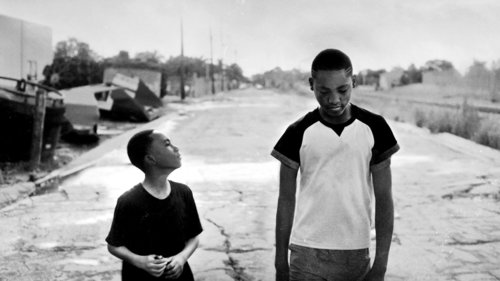 Two young people walking on an empty street