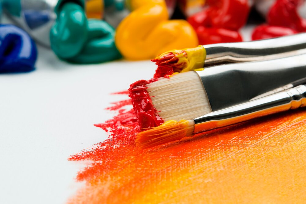 Paint brushed covered in red, orange, and yellow paint with squeezed multi-colored paint tubes in the background.