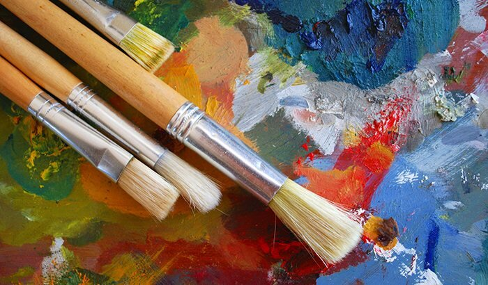 Paintbrushes lying on top of a multicolored painted surface