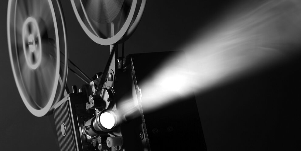 A black and white photograph of a film projector projecting light
