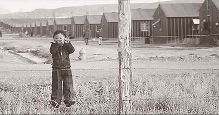 A sepia image from the film 'The Film Our Lost Years' featuring a child behind a barbed wire fence with an encampment in the backgrounds