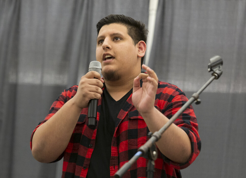 A speaker wearing a red and black plaid flannel and speaking into the microphone in one of their hands while making a gesture with their other hand