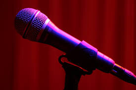 A microphone illuminated by a pink light with red curtains in the background