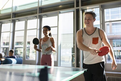 Two people smiling while playing table tennis in the Campus Recreation Center