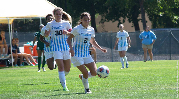 Two people on the women's soccer team kicking a soccer ball while wearing soccer uniforms