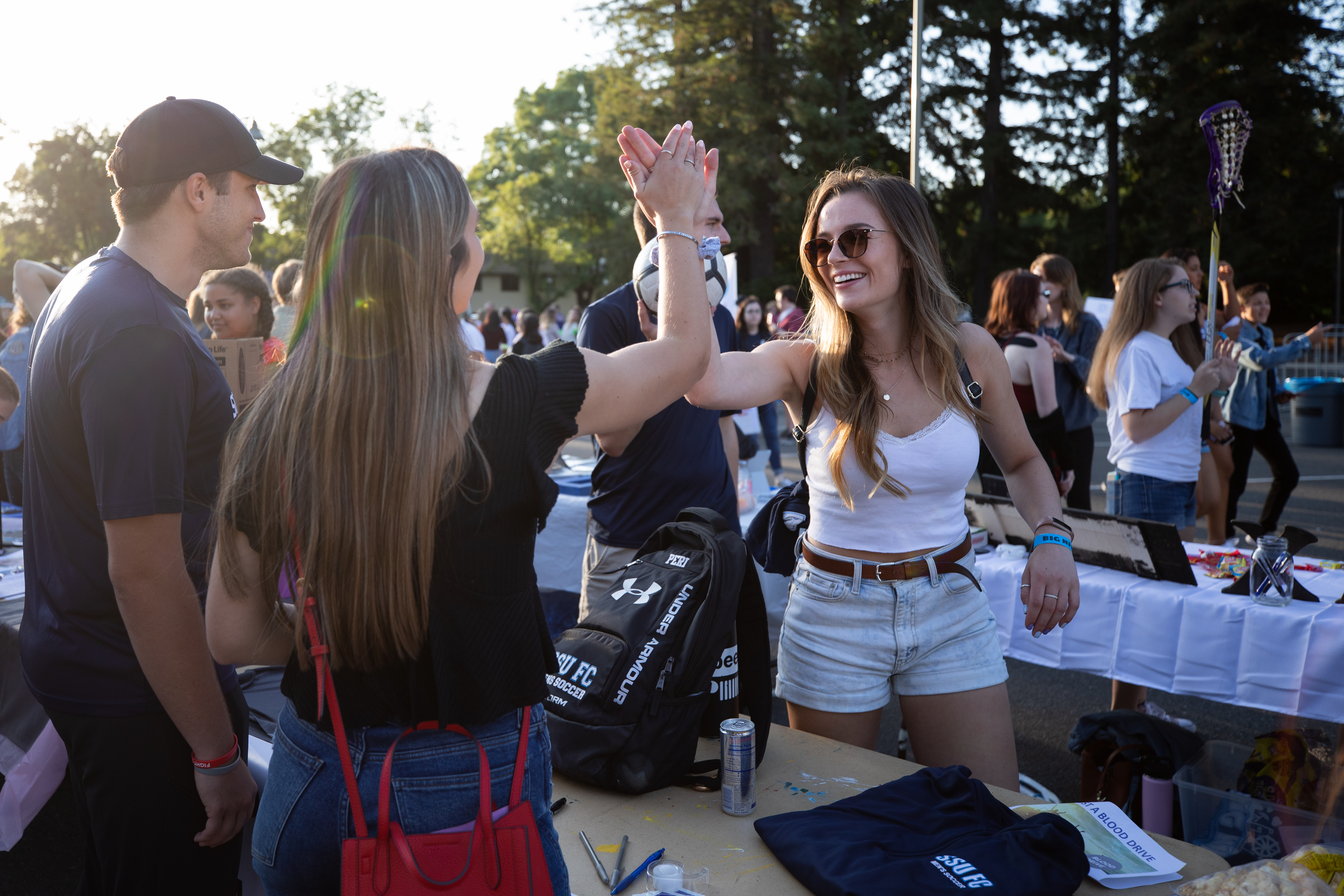Students in a crowded outdoor setting smiling and giving each other high-fives