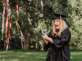 A graduate with a surprised expression popping a confetti party popper while wearing a graduation cap and gown