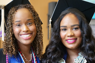 Two female graduates smile for the camera