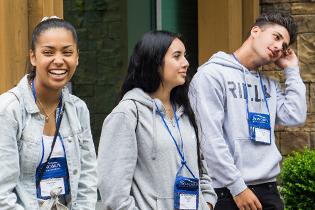 Three students with orientation lanyards around their necks