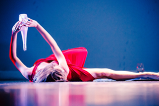 dancer in red dress holding glass bottle while laying on the stage